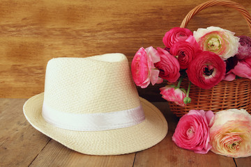 image of beautiful flowers next to fedora hat. vintage filtered