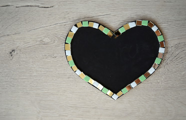 Heart shaped chalk board on wood background