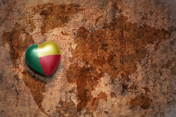heart with national flag of benin on a vintage world map crack paper background.