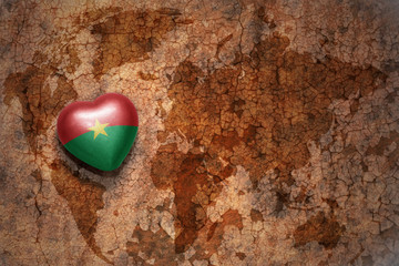 heart with national flag of burkina faso on a vintage world map crack paper background.