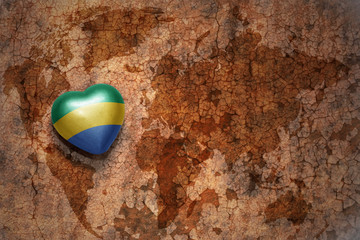 heart with national flag of gabon on a vintage world map crack paper background.