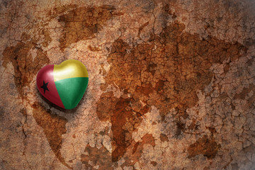 heart with national flag of guinea bissau on a vintage world map crack paper background.