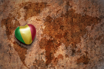 heart with national flag of mali on a vintage world map crack paper background.