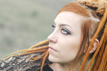 Redhead girl with dreadlocks and blue eyes looking up