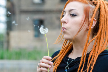 Red-haired girl with dreadlocks blowing dandelion