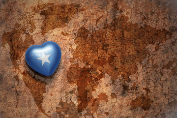heart with national flag of somalia on a vintage world map crack paper background.
