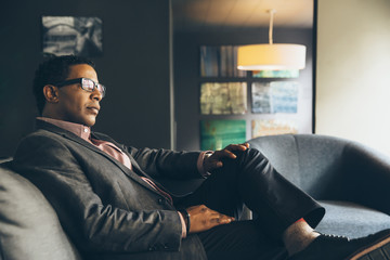 Mixed race businessman sitting in office lobby