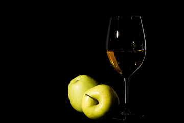 Green apples and wine glass with juice on black
