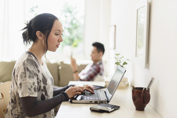 Woman using laptop at desk in living room