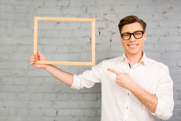 Handsome man in glasses  pointing on wooden frame in his hand