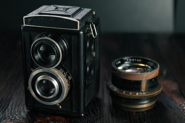 The old film camera and the lens on the wooden table.