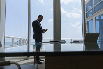 Hispanic businessman using cell phone in conference room
