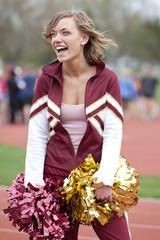 Caucasian cheerleader smiling on track