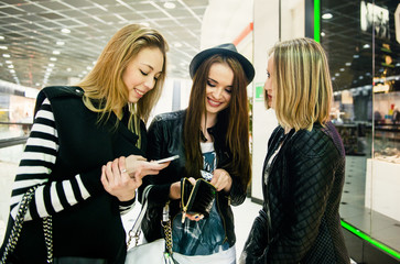 Caucasian women using cell phones in shopping mall