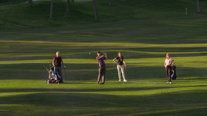 Caucasian friends playing golf on course