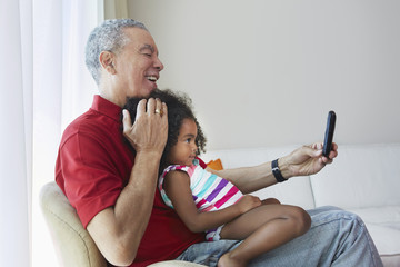 Grandfather and granddaughter taking selfie in living room
