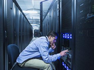 Hispanic technician checking technology in server room