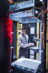 Hispanic technician using computer in server room