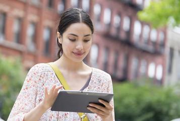 Hispanic woman using digital tablet in city