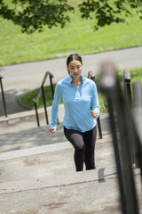 Hispanic woman jogging on city steps