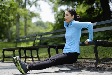 Hispanic woman doing push-ups on park bench