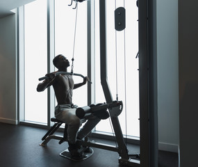 African American athlete using exercise machine in gym