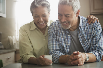 Hispanic couple using cell phone in kitchen