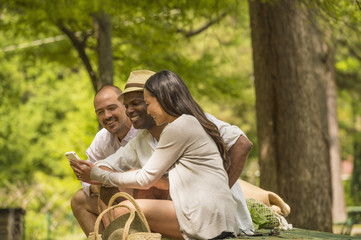Friends using cell phone on picnic table