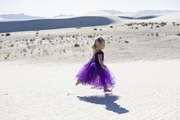 Caucasian girl walking on desert sand dunes
