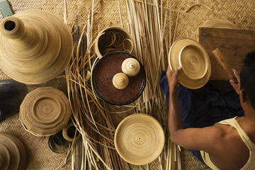 Artisan weaving traditional baskets in workshop
