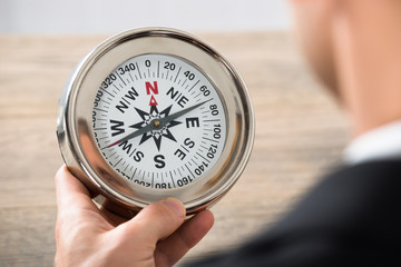 Close-up Of Businessman Holding Compass In Office