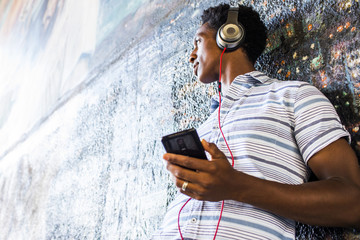 Man listening to cell phone by mural