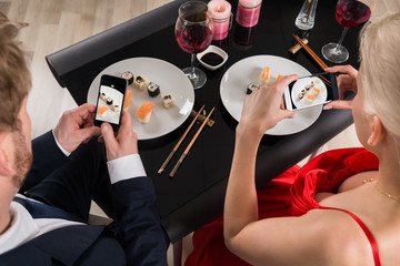 Couple Making Picture Of Food With Their Smartphones