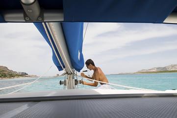 Man hoisting sailboat rigging on deck