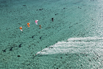 Aerial view of people kitesurfing on ocean