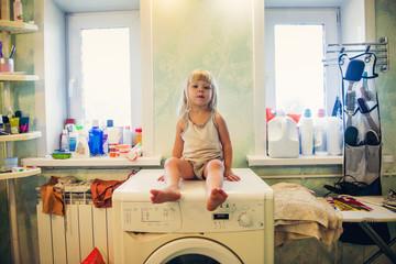 Caucasian girl sitting on washing machine