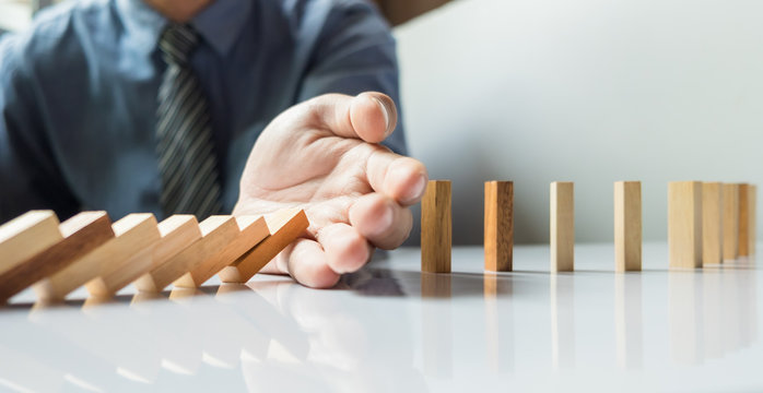 businessman hand stop dominoes continuous toppled or risk with c