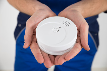 Close-up Of Electrician Holding Smoke Detector