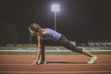 Mixed race runner in starting position on sports field