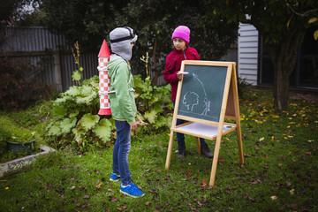 Children planning jetpack rocket at garden