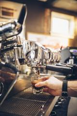 Caucasian barista pouring espresso shot in cafe