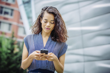 Mixed race businesswoman using cell phone outdoors