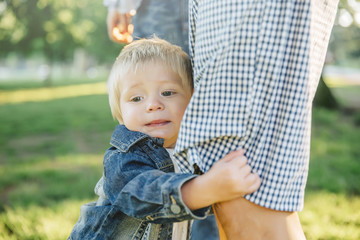 Boy clutching leg of father in grass in park