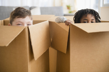 Close up of boys playing in cardboard boxes