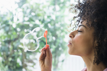 Mixed race woman blowing bubbles
