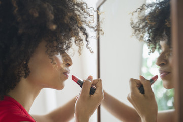 Mixed race woman applying lipstick in mirror