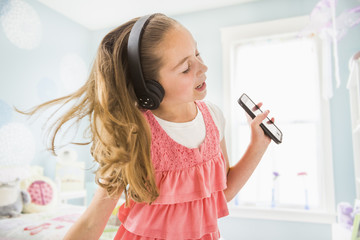 Caucasian girl singing to wireless headphones
