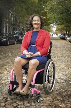 Disabled woman smiling in wheelchair on cobblestone street