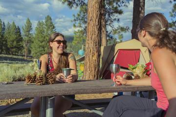 Caucasian women drinking wine at campsite
