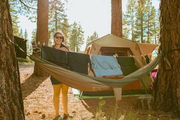 Caucasian woman hanging laundry at campsite